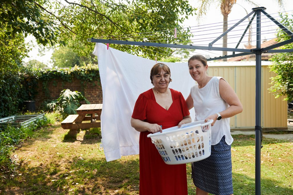 Lady with red dress with carer at washing line